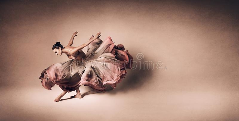 Graceful woman dancing in flowing dress stock images