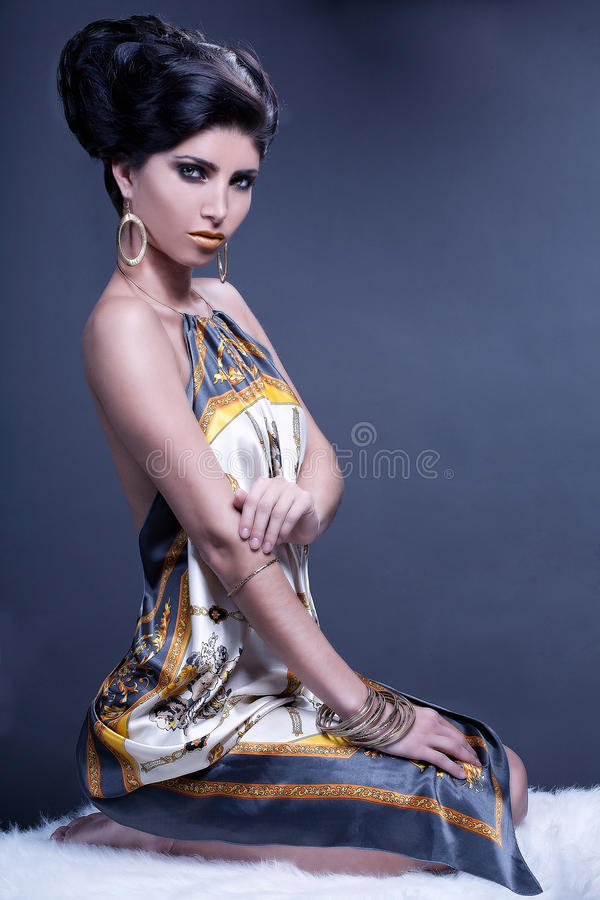 Graceful Woman On The Fur. Elegant graceful woman sitting on the fur royalty free stock image