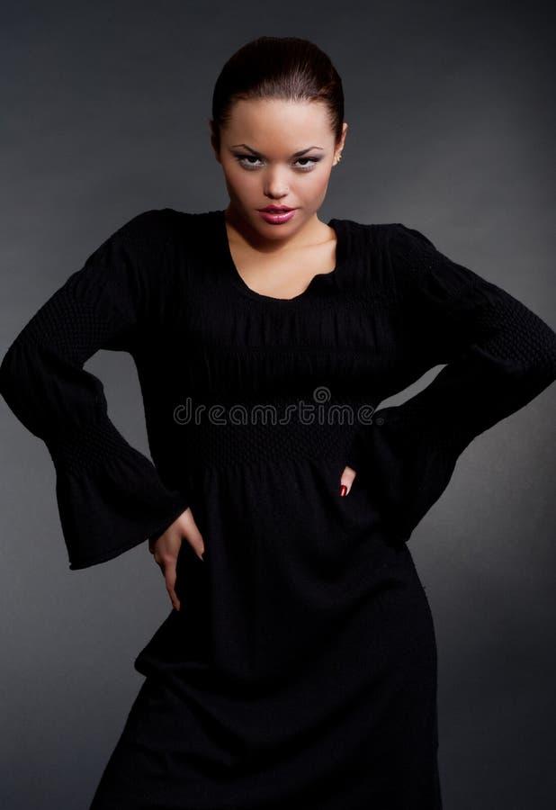 Graceful Woman Posing Against Dark Background Royalty Free Stock Image