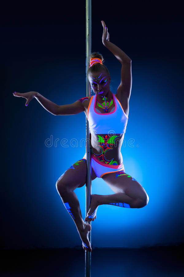 Graceful young pole dancer with fluorescent makeup stock photos