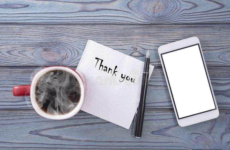 Gracias, en una servilleta en una tabla de madera con una taza de café imagenes de archivo