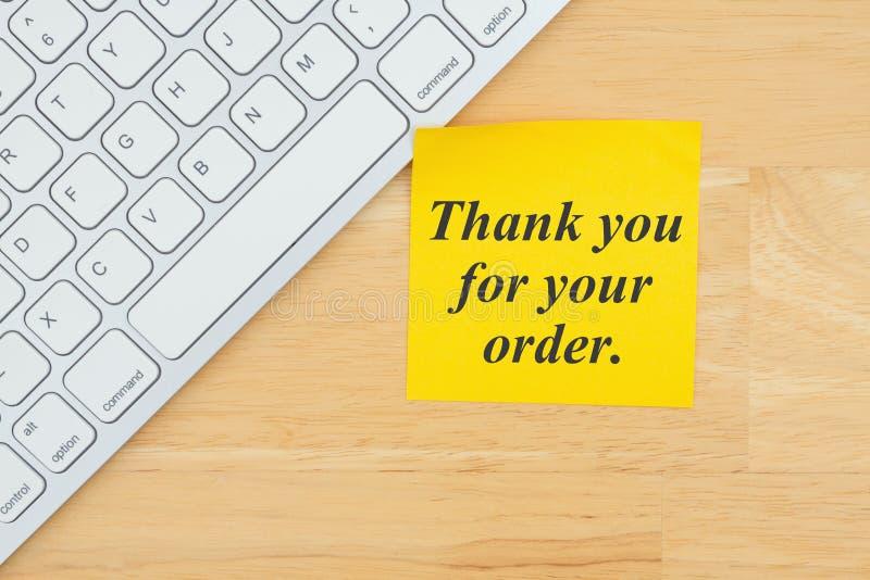 Gracias por su texto de la orden en una nota pegajosa con un teclado imagen de archivo libre de regalías