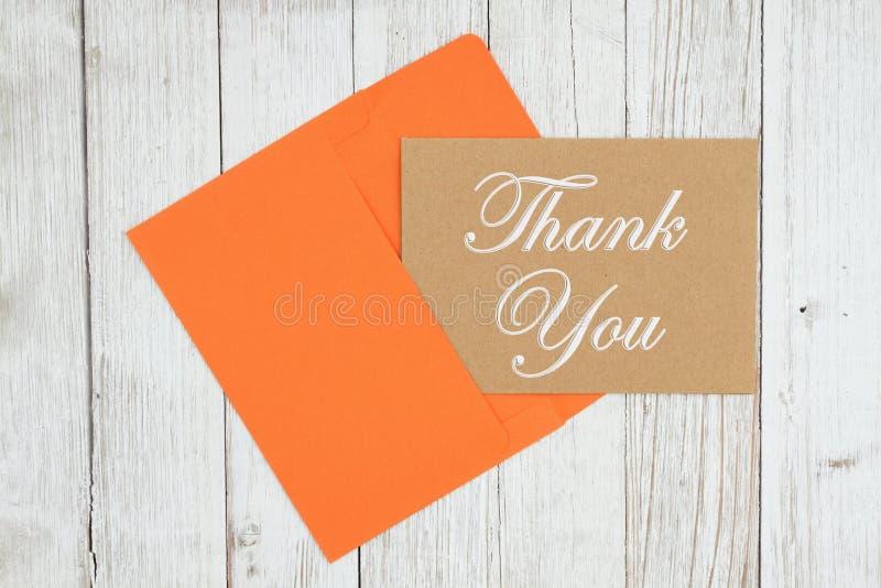 Gracias tarjeta de felicitación marrón con el sobre en la madera resistida texturizada de la lechada de cal foto de archivo