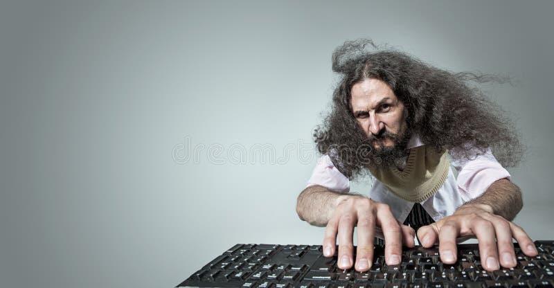 Gracioso retrato de un nerd flaco que trabaja con una computadora imagenes de archivo