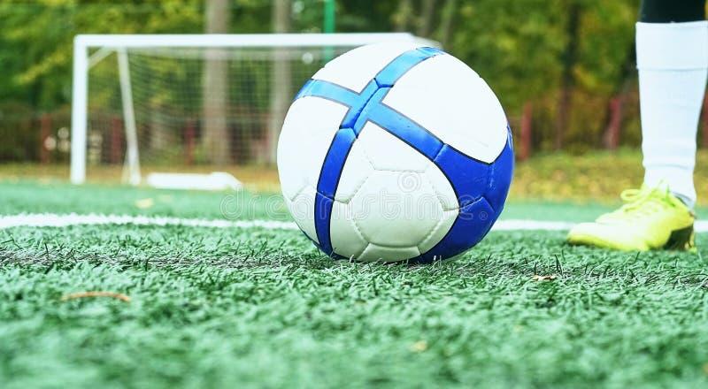 Gracz futbolu przygotowywający uderzać białą piłkę z błękitnymi lampasami Futbolowa brama w tle obraz royalty free