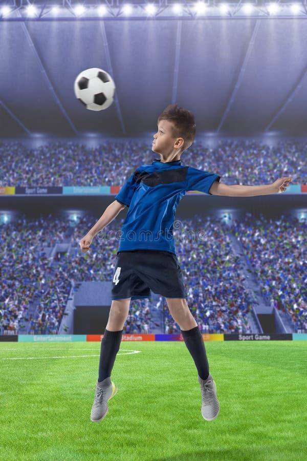 Gracz futbolu uderza piłkę z głową na stadium piłkarski zdjęcie stock
