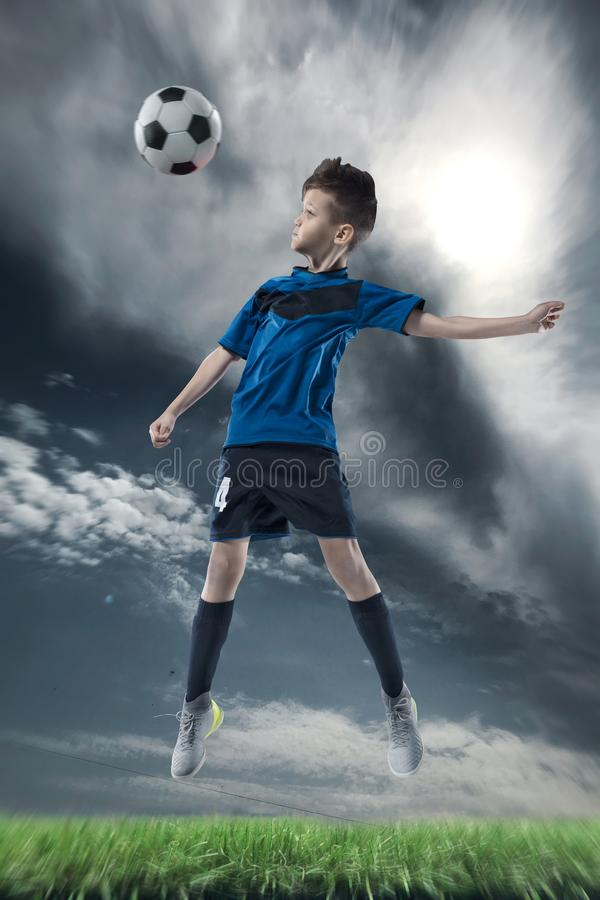 Gracz futbolu uderza piłkę z głową na stadium piłkarski zdjęcie royalty free