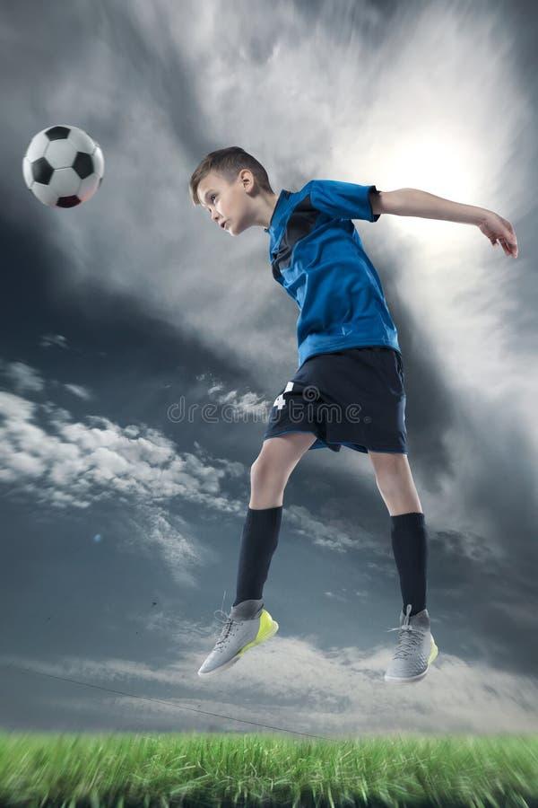 Gracz futbolu uderza piłkę z głową na stadium piłkarski obrazy stock