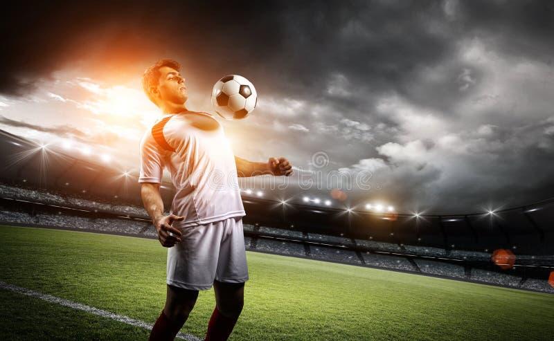 Gracz futbolu wytrzymywa piłkę z jego klatką piersiową w stadium zdjęcie royalty free