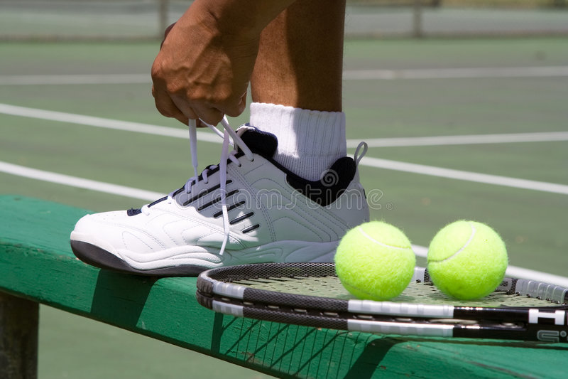 gracz horyzontalnej zawiązać buta tenisa zdjęcie royalty free