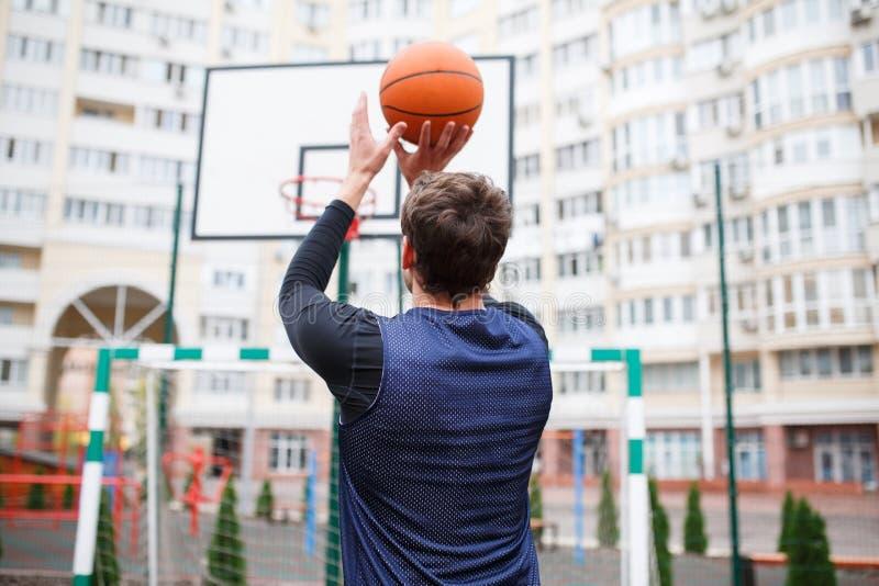Gracz koszykówki przy plenerowym stadium trenuje, rzucający piłkę w pierścionek, podnosi jego ręki up obraz stock