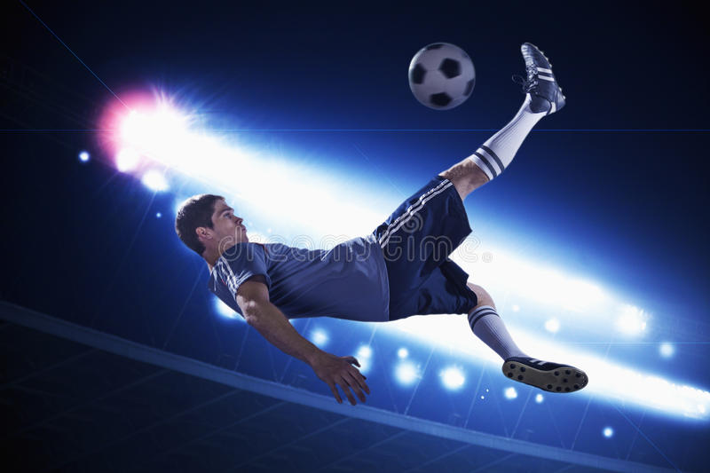 Gracz piłki nożnej kopie piłki nożnej piłkę w w połowie powietrzu, stadium zaświeca przy nocą w tle obraz stock