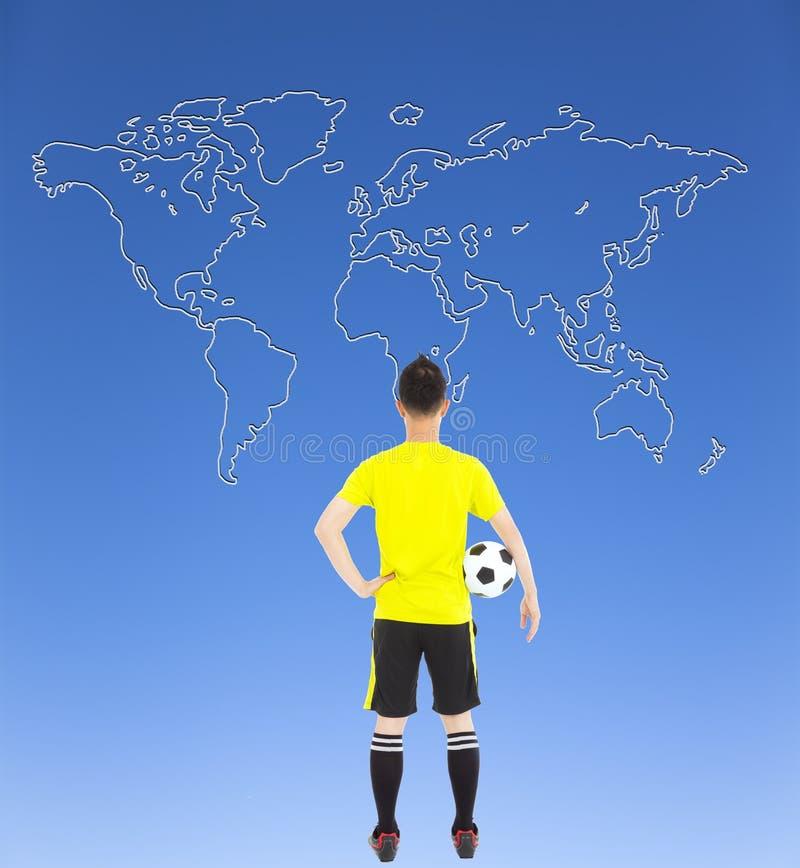 Gracz piłki nożnej trzyma przyglądającą globalną mapę i piłkę nożną fotografia royalty free