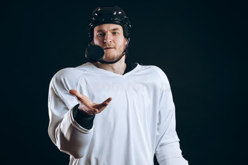 Gracz w hokeja gryźć krążek hokojowego z łamanymi zębami i patrzeć kamerę z uśmiechem obraz stock