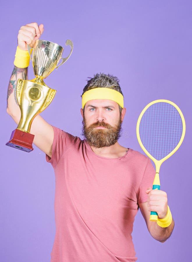 Gracz w tenisa wygrany mistrzostwo Atleta chwyta tenisowy kant i z?ota czara M??czyzny modnisia odzie?y sporta brodaty str?j fotografia stock