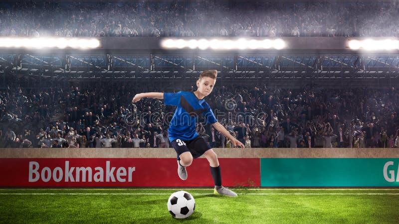 Gracza futbolu dzieciak drybluje na stadium piłkarski zdjęcie royalty free