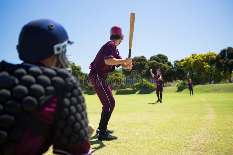 Gracze bawić się baseballa na polu wpólnie obrazy stock