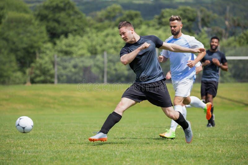 Gracze futbolu bawić się piłkę nożną w ziemi fotografia stock