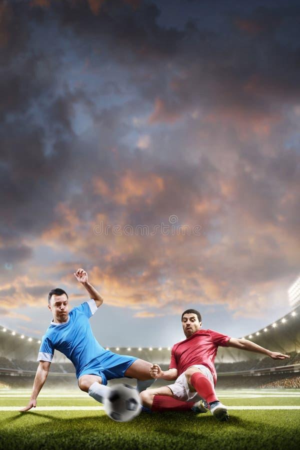 Gracze piłki nożnej w akci na zmierzchu stadium tle fotografia stock