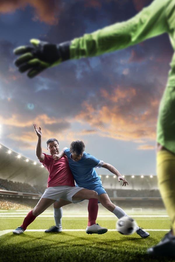 Gracze piłki nożnej w akci na zmierzchu stadium tle obrazy royalty free