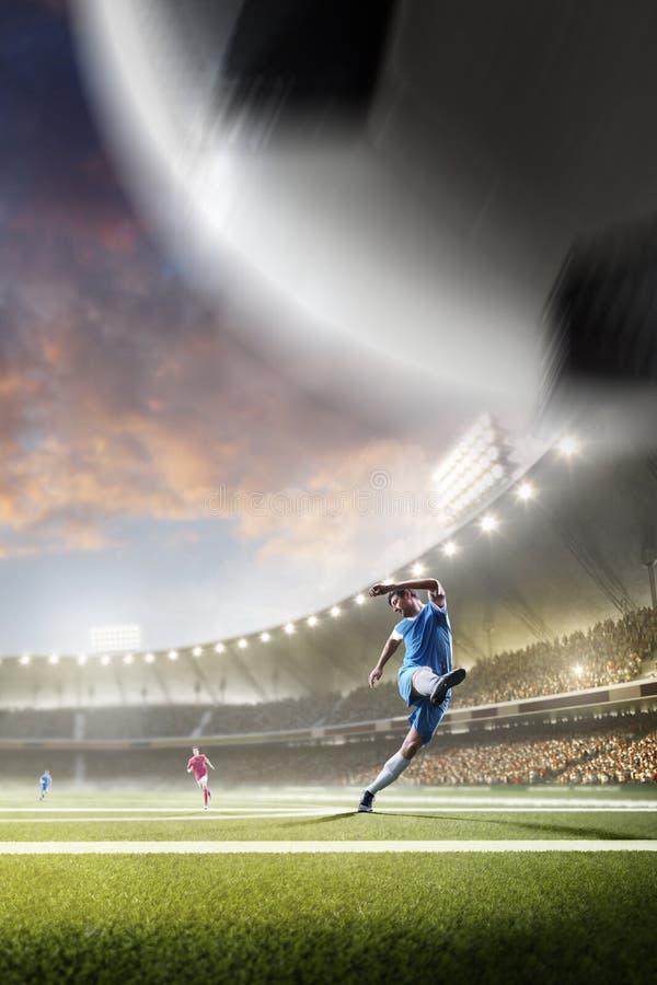 Gracze piłki nożnej w akci na zmierzchu stadium tle zdjęcia royalty free
