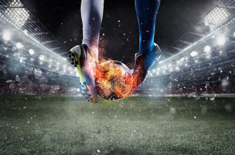 Gracze piłki nożnej z soccerball na ogieniu przy stadium podczas dopasowania zdjęcie royalty free