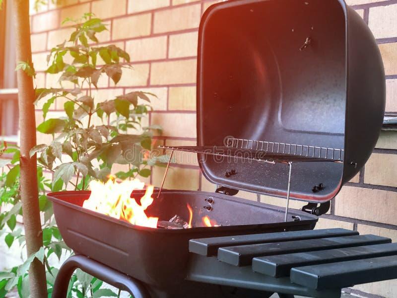 Grade aberta perto da casa de campo com carvão vegetal ardente para dentro dele Apronte para cozinhar a carne crua Do BBQ do verã fotos de stock