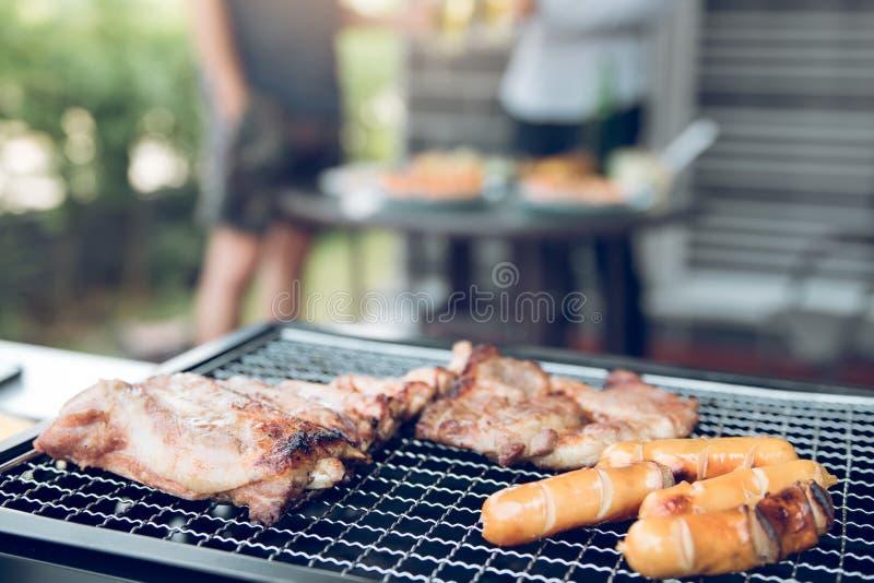 A grade ascendente próxima com carne e a salsicha pronta para socializar comemoram com os amigos na casa do outsite imagem de stock royalty free