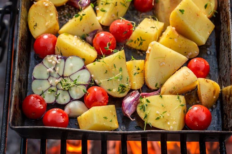 Grade cozida saboroso do na das batatas com tomates, alho e alecrins imagem de stock