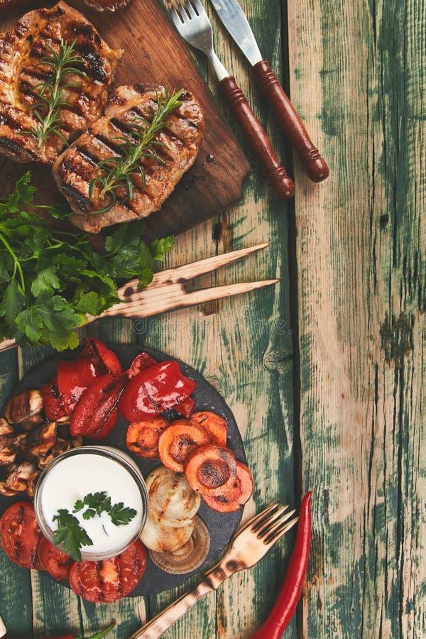 Grade da carne de porco do bife na placa de corte de madeira com uma variedade de vegetais grelhados foto de stock