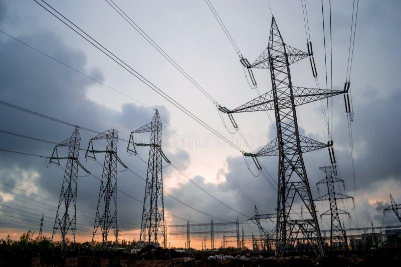 Grade de eletricidade de alta tensão das linhas elétricas, com as nuvens tormentosos que quebram distante no por do sol Torres  imagens de stock royalty free