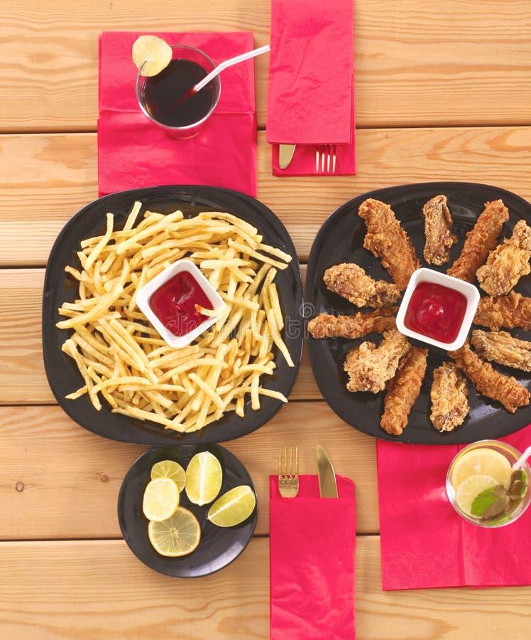 Grade e batatas fritas da galinha na tabela foto de stock royalty free