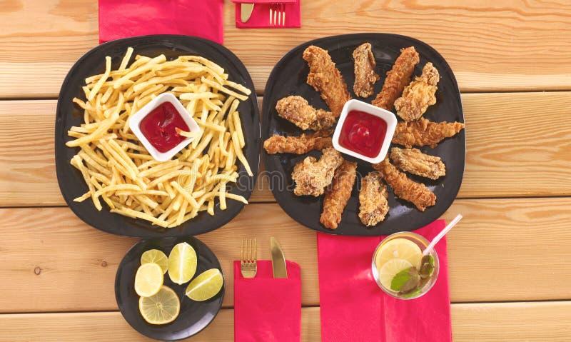 Grade e batatas fritas da galinha na tabela fotografia de stock
