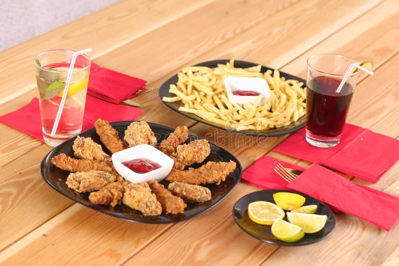 Grade e batatas fritas da galinha na tabela fotografia de stock royalty free