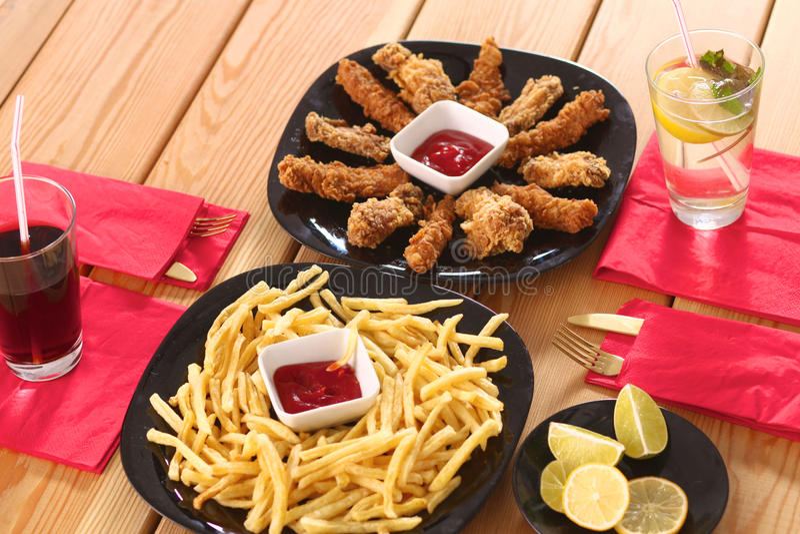 Grade e batatas fritas da galinha na tabela imagem de stock royalty free