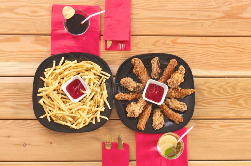Grade e batatas fritas da galinha na tabela fotos de stock