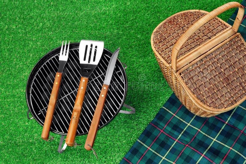 Grade portátil do assado no gramado, nas ferramentas, na cesta do piquenique e no Blanke fotos de stock royalty free