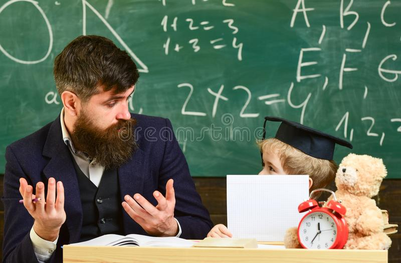 Grade school concept. Kid studies with teacher, listening with attention. Father teaches son elementary knowledge. Discuss, explain. Teacher and pupil in royalty free stock image