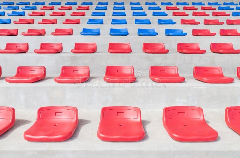 Gradería cubierta plástica de los asientos del deporte rojo y azul en estadio público del deporte foto de archivo