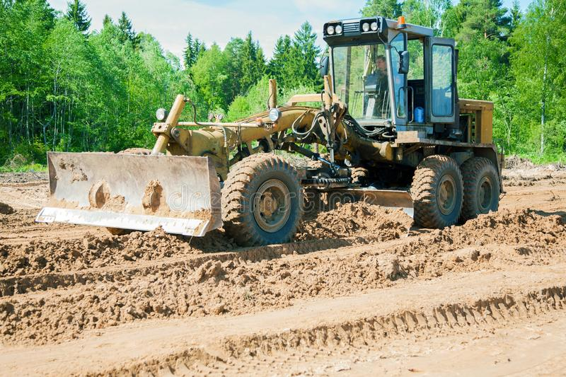 The grader clears away a ground. In the afternoon royalty free stock image