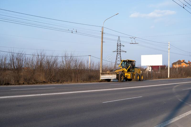 Grader is working on road construction. Grader industrial machine on construction of new roads. Heavy duty machinery. Working on highway. Construction equipment stock image