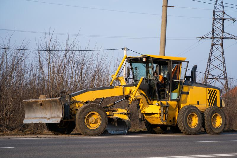 Grader is working on road construction. Grader industrial machine on construction of new roads. Heavy duty machinery. Working on highway. Construction equipment stock photos