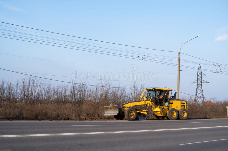 Grader is working on road construction. Grader industrial machine on construction of new roads. Heavy duty machinery. Working on highway. Construction equipment royalty free stock photo