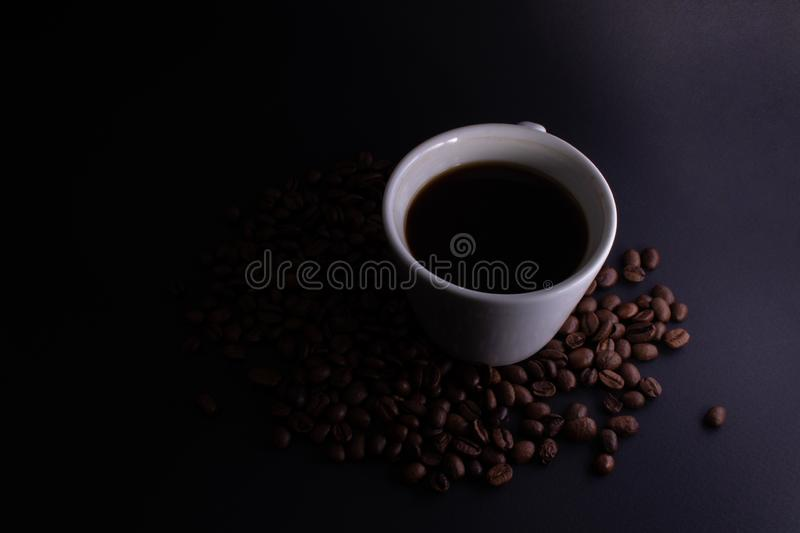 Gradient lighting of a cup with black strong coffee on a dark background with strewn coffee beans.  stock images
