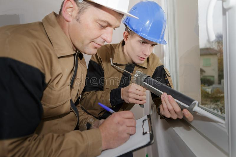 Grading apprentice`s window installation. Grading the apprentice`s window installation royalty free stock photography