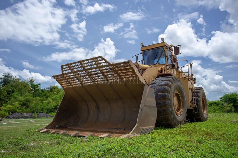 Grading bucket of a yellow bulldozer in the field.  stock photo