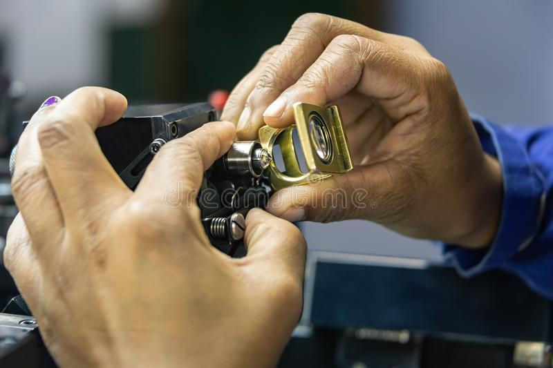 Grading clarity on diamonds. Microscope and magnifying glass, african woman working stock photos
