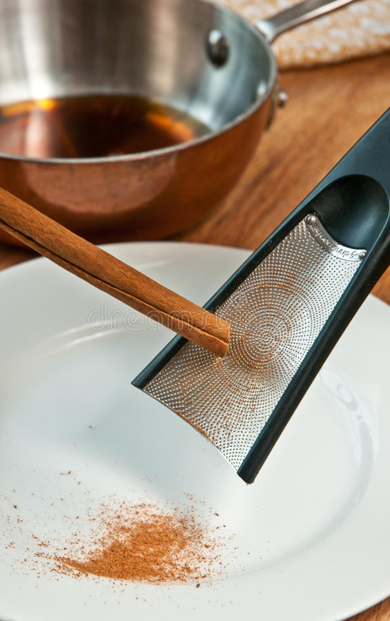Grading fresh, organic cinnamon. With a stainless steel grater on to a round white plate with a pan of warm maple syrup all on a wood serving board royalty free stock photo
