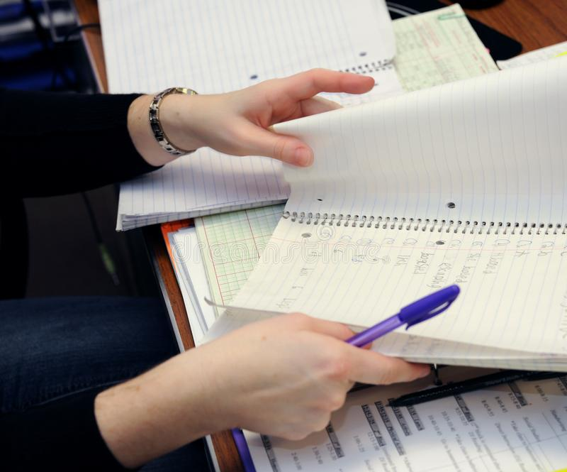 Grading Homework Papers. Teacher sits in her classroom grading homework papers.  She is flipping pages in students notebook stock photos