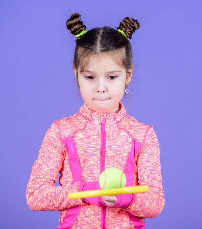 Gradisco giocar a tennise Giocatore di tennis sveglio Bambino della bambina nel club di sport Addestramento di sport per i bambin immagini stock libere da diritti